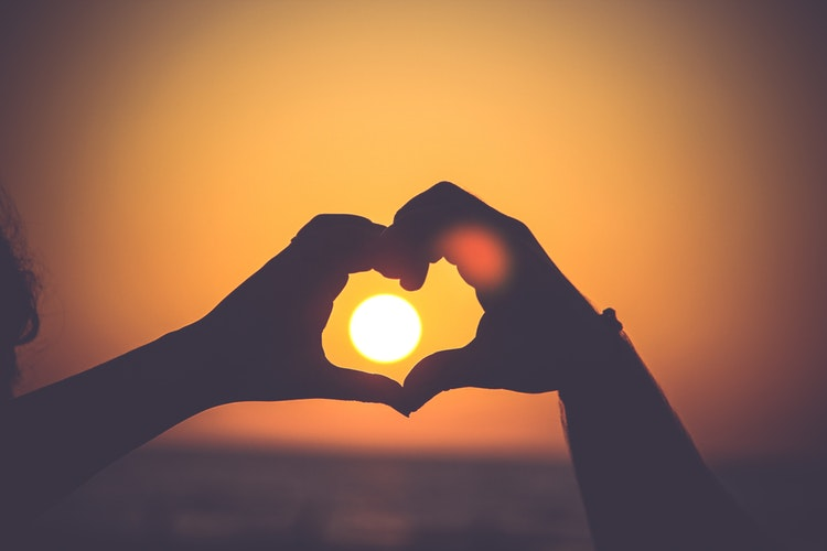 hands shaped in heart, framing the sun