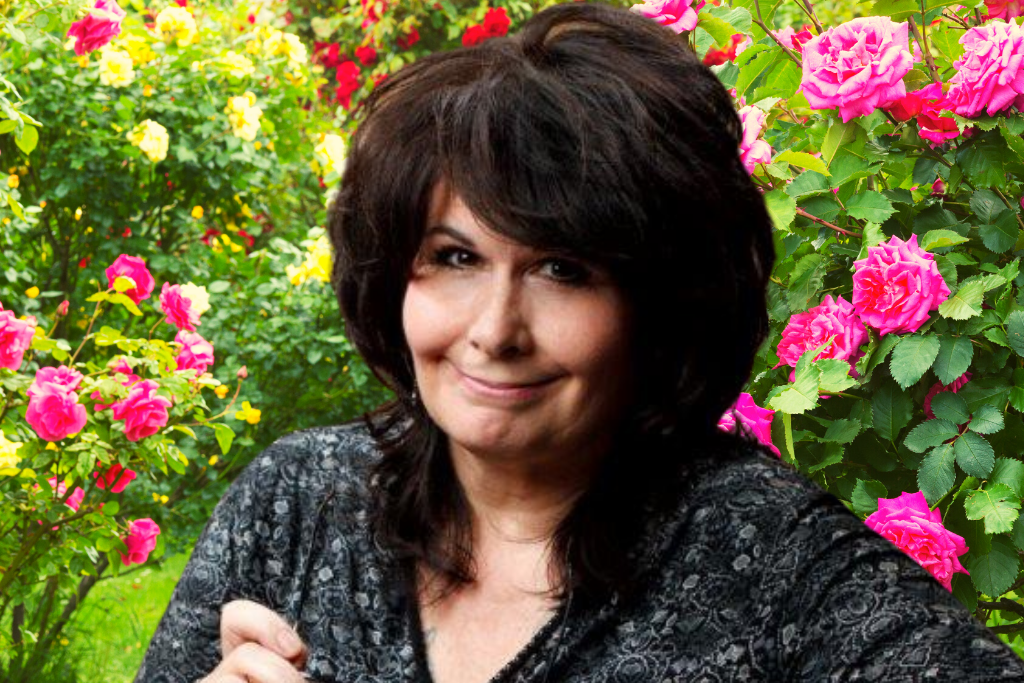 Jeanne Fritch, Conscious Relationships Mentor, sitting in a garden of roses