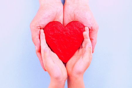 two sets of hands holding heart